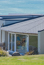 Impact Roofing - thumbnail image of a house by the sea roofed by Impact